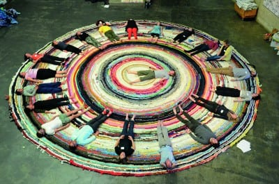 "Christian Nagler, Yoga for Adjuncts, 2014, at the Valuing Labor in the Arts Practicum, UC Berkeley Art Museum, April 19, 2014 (photographs © Megan Hoetger, provided by the artist).  Rug: Fritz Haeg, Domestic Integrity Field, 2012–14, crocheted and spirally stitched rug created from local textiles by volunteers, on view January 29–June 1, 2014 (artwork © Fritz Haeg).  The rugs in Haeg's Domestic Integrities project, which expand as they travel from city to city, function ""as charged sites for testing, performing, and presenting how we want to live."""