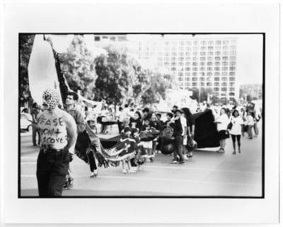 Guillermo Gómez-Peña, Please Don't Discover Me/Passa Calle, 1992, black-and-white photograph, opening procession, National Association of Artists Organizations Conference, Austin, Texas, 1992 (artwork © Guillermo Gómez-Peña; photograph provided by the Portal to Texas History, University of North Texas, http://texashistory.unt.edu/ark:/67531/metapth304065/)