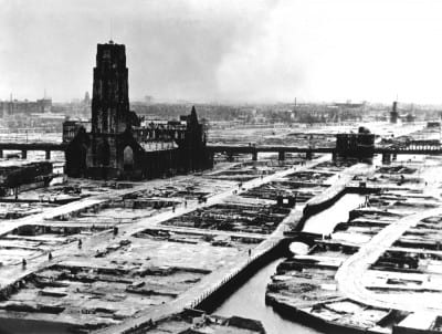 "Aerial view of the ruins of Rotterdam, 1940,  photograph. U.S. National Archives and Records Administration, 208-PR-10L-3 (photograph in the public domain)  Central Rotterdam with Laurenskerk. From the contemporary caption: ""The German ultimatum ordering the Dutch commander of Rotterdam to cease fire was delivered to him at 10:30 a.m. on May 14, 1940. At 1:22 p.m., German bombers set the whole inner city of Rotterdam ablaze."""