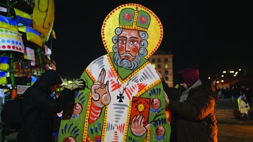 Roman Zilinko, Ostap Lozynskyi, and Olexander Bryndikov, Saint Nicholas, 2013, acrylic on particle board, 8 ft. 3 in. x 49 in. (252 x 125 cm), installation view of the green side, Independence Square, Kyiv, Ukraine (artwork © Roman Zilinko, Ostap Lozynskyi, and Olex-ander Bryndikov; photograph © Ivan Yasniy)