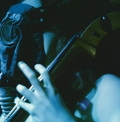 <strong>Dick Preston, Charlotte Moorman performing Aria II of <em>Opera Sextronique</em>, with army-issue gas mask, 1967,</strong> color photograph of performance, Film-Maker's Cinematheque, New York City (photograph © Estate of Dick Preston; photograph provided by Charlotte Moorman Archives, Charles Deering McCormick Library of Special Collections, Northwestern University Library, Evanston, IL)