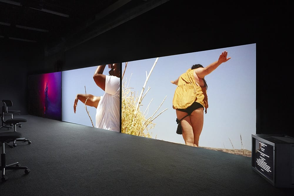 A.K. Burns, installation view of A Smeary Spot, 2015, four-channel video installation, dimensions variable (artwork © A.K. Burns, image provided by the artist, Callicoon Fine Arts, NY, and Michel Rein Gallery, Paris/Brussels).Videos 1–3: HD color, six-channel sound, TRT 53:13 minute synchronized loop; video 4: SD b/w, silent, TRT 4:00 minute loop. Videos 1–3 are each projected onto 81 x 144 in. (205.7 x 365.7 cm) walls, built at an angle to the gallery walls. Gallery is painted black with black industrial carpeted floor and twelve office chairs for seating. Video 4 is presented on a separate 29 in. (73.6 cm) Sony cube-monitor.