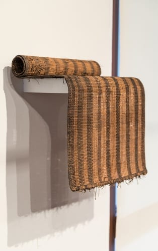 Unidentified Artist, Tuareg (Mali, Niger), smaller prayer mat shown rolled on shelf, ca.1970s, reed and leather, installation view, Made to Move: African Nomadic Design, Handwerker Gallery, 2017. Collection of Herbert F. Johnson Museum of Art (photograph by Risham Majeed)