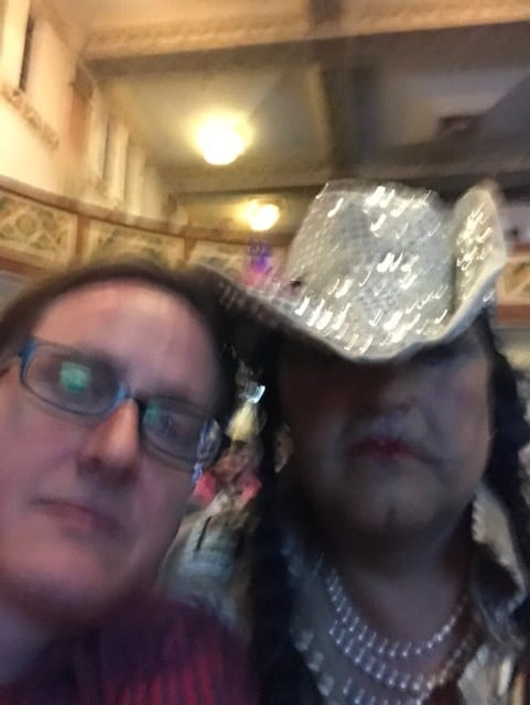 Here is a blurry, yet zoomed-in, close-up perspective of curator Joey Orr alongside Adrian Stimson as Buffalo Boy. The two of them are posing during Buffalo Boy's mid-performance selfie session. Orr, on the left, is wearing dark rimmed glasses with a serious expression. Buffalo Boy dons a similar expression in contrast to the glittery cowboy hat that is dipped forward, successfully covering most of both eyes. We see red lips, a pronounced chin dimple, and two long dark brown braids. Buffalo Boy is also wearing a pearl necklace and is head-to-head with Orr.