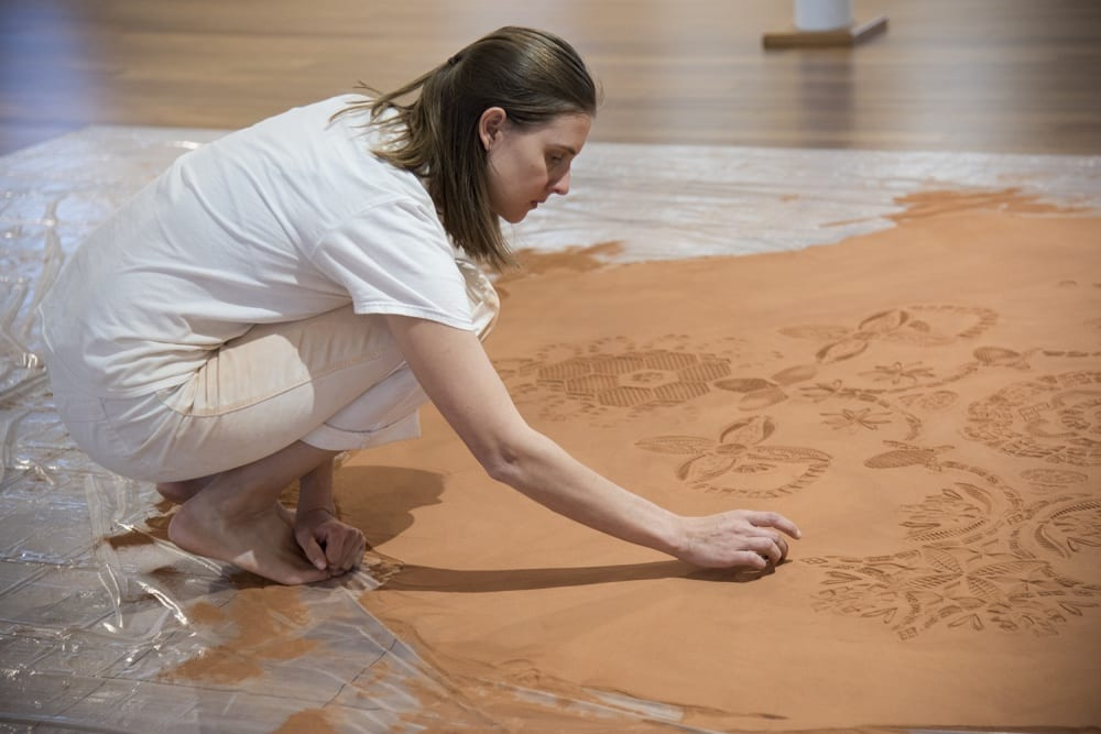 "Rena Detrixhe, a visiting artist in the Department of Visual Art, installs her ""Red Dirt Rug"" at The Commons at the University of Kansas. She is crouched over her bent knees, wearing all white, which has begun to turn the color of the red dirt during the installation process. Detrixhe's left hand rests on her bare feet as her right hand makes an impression in the dirt that is part of the larger emerging pattern."