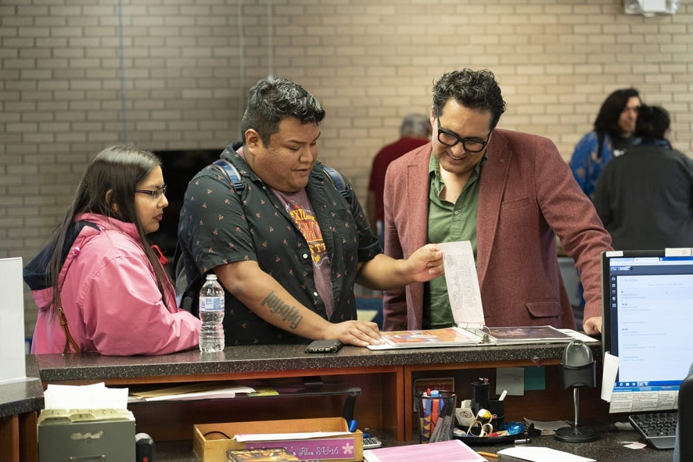 Three people are standing at the circulation desk in the Haskell Indian Nations University library. Adrian Stimson stands on the right in conversation with two students. There is a photo album on the desk, and as Stimson looks through it, the two students next to him, a man and a woman, guide his gaze by pointing out interesting details. The middle figure in the photograph, the young man, lifts a page of the album with his left hand while his right one rests on the circulation desk. All three people look downward at the album as Stimson smiles. On the circulation desk itself we see a computer screen, writing utensils, a plastic water bottle, and a cell phone.