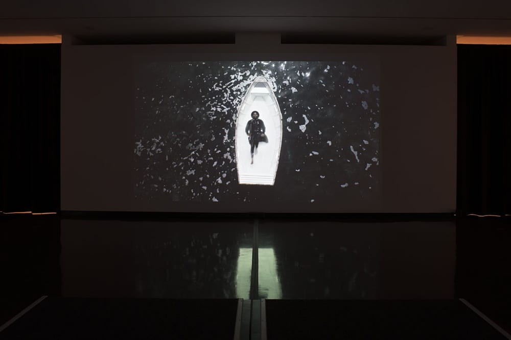 "This still image captures a moment in the three-channel video installation ""Passage"" by Mohau Modisakeng. There are two projected videos playing outside of this frame to the left and right. In this photograph, we see Modisakeng from a top-down point of view, clad in black clothing, a black hat, and barefoot. He is laying on his back in a white boat that is floating in a sea of black, grey-colored water. His arms are by his side and one his legs is bent with the flat of his foot resting next to his knee."