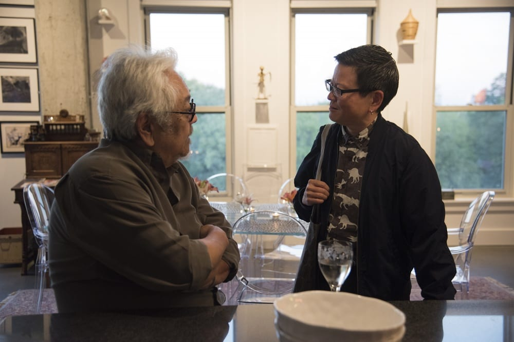 Two artists, Roger Shimomura and Tina Takemoto, are standing close to a countertop in deep conversation. They are located in a residential home where Shimomura is depicted sitting and glancing slightly upwards in conversation with Takemoto. There are three large vertically shaped windows in the background spanning the wall. The windows allow for daylight to flood through into the living space. Three framed works of art and an antique piece of furniture are in the background to the left of Shimomura.