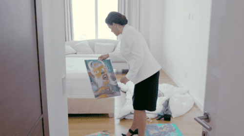 The broker examines one of the various artworks that have appeared unexpectedly throughout the apartment.