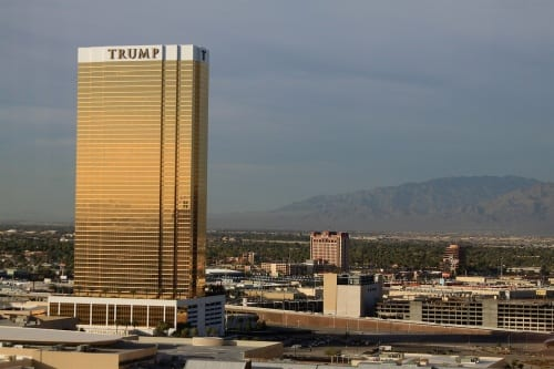 "The ""piss-yellow gold"" Trump International Hotel in Las Vegas, with Trump's name proudly emblazoned on its crown, rises against a mountainous desert backdrop."