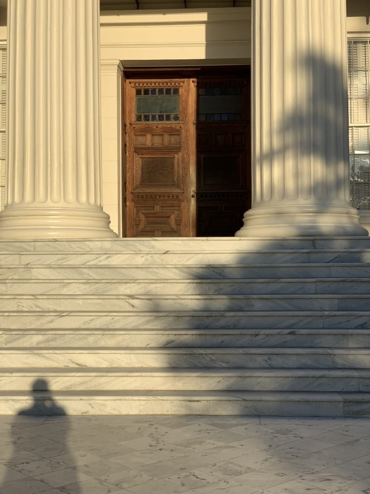 View of the steps at sunset, with the woden door to the Capitol partially open