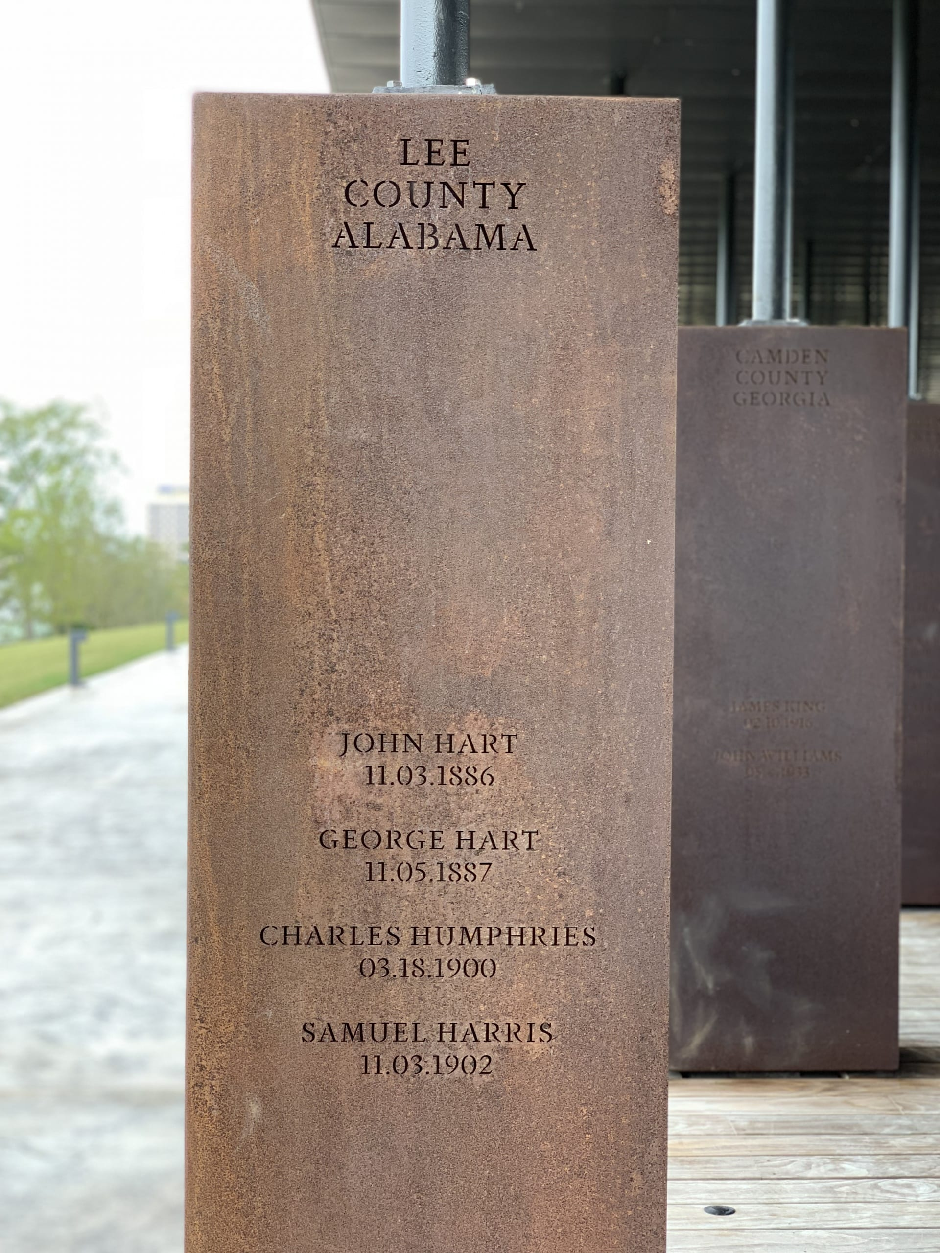 "detail of a memorial stele ""Lee County Alabama"" with names of 4 lynching victims"