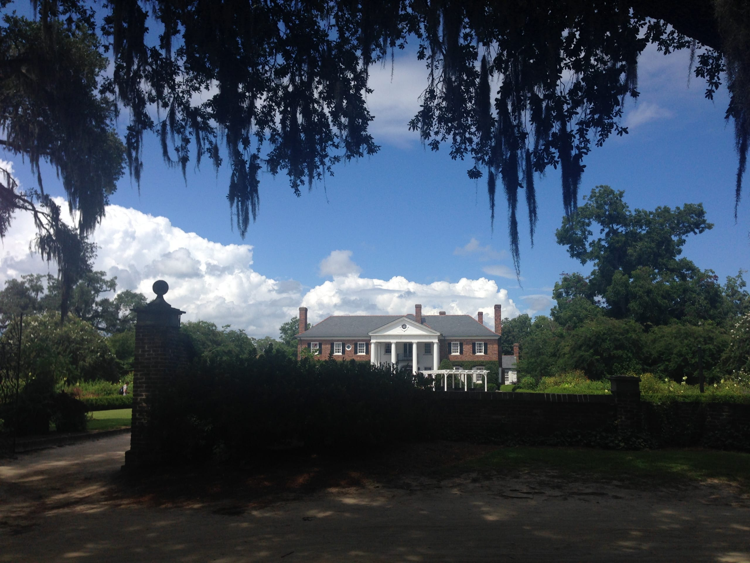 view of a handsome Georgian manor framed through Spanish Moss