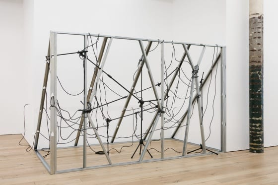 An art installation constructed of vertical metal studs and mic stands, intertwined with black electrical cables