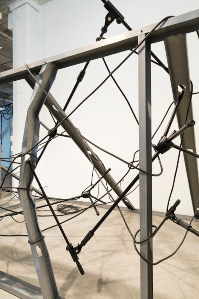 Detail of an art installation constructed of vertical metal studs and mic stands, intertwined with black electrical cables