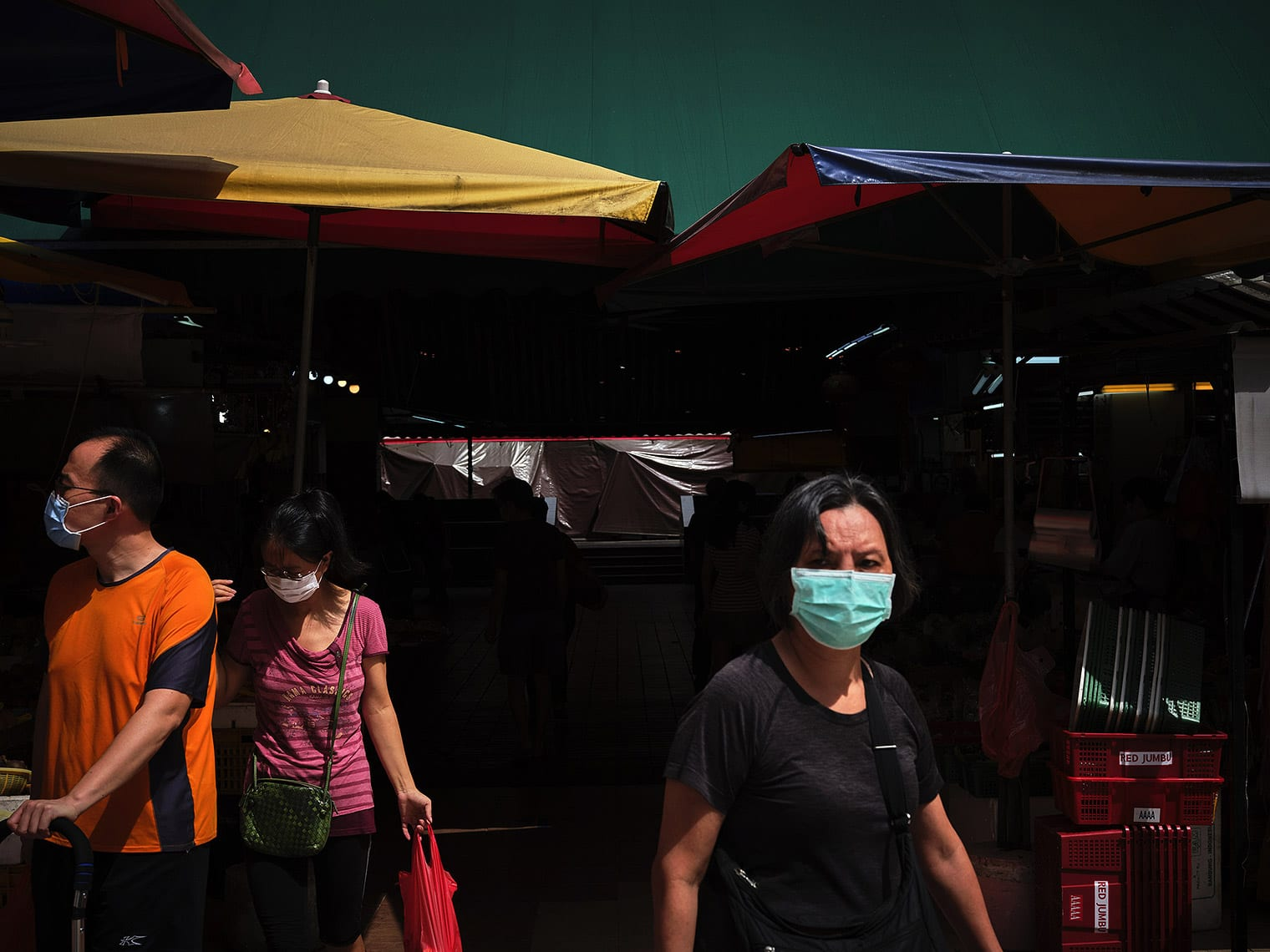 Masked shoppers stand under awnings at a Singapore wet market
