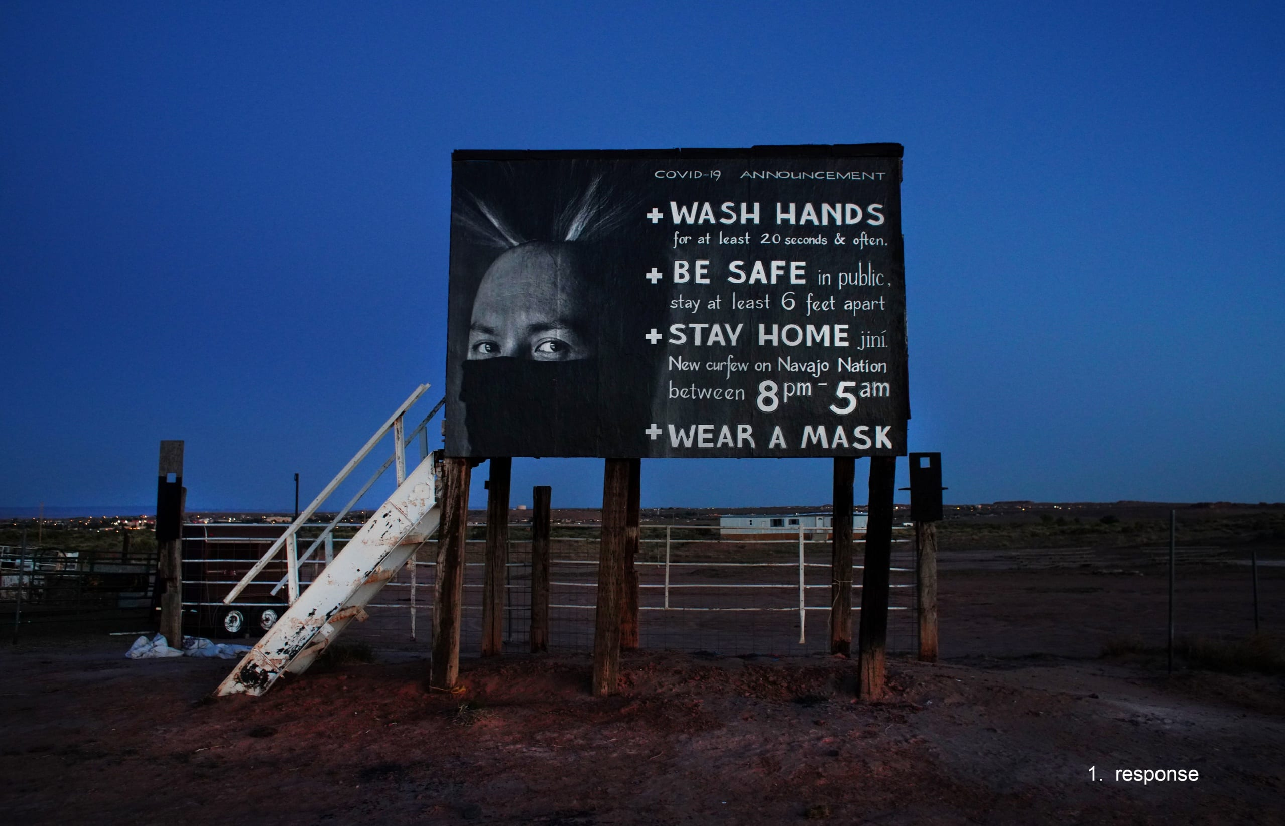 Color photograph, taken in pre-dawn light, of the Diné COVID PSA Poster (featuring the face of a Navajo man and instructions for staying safe from the coronavirus), installed on of a rodeo announcer's stand on the Navajo nation in Tuba City