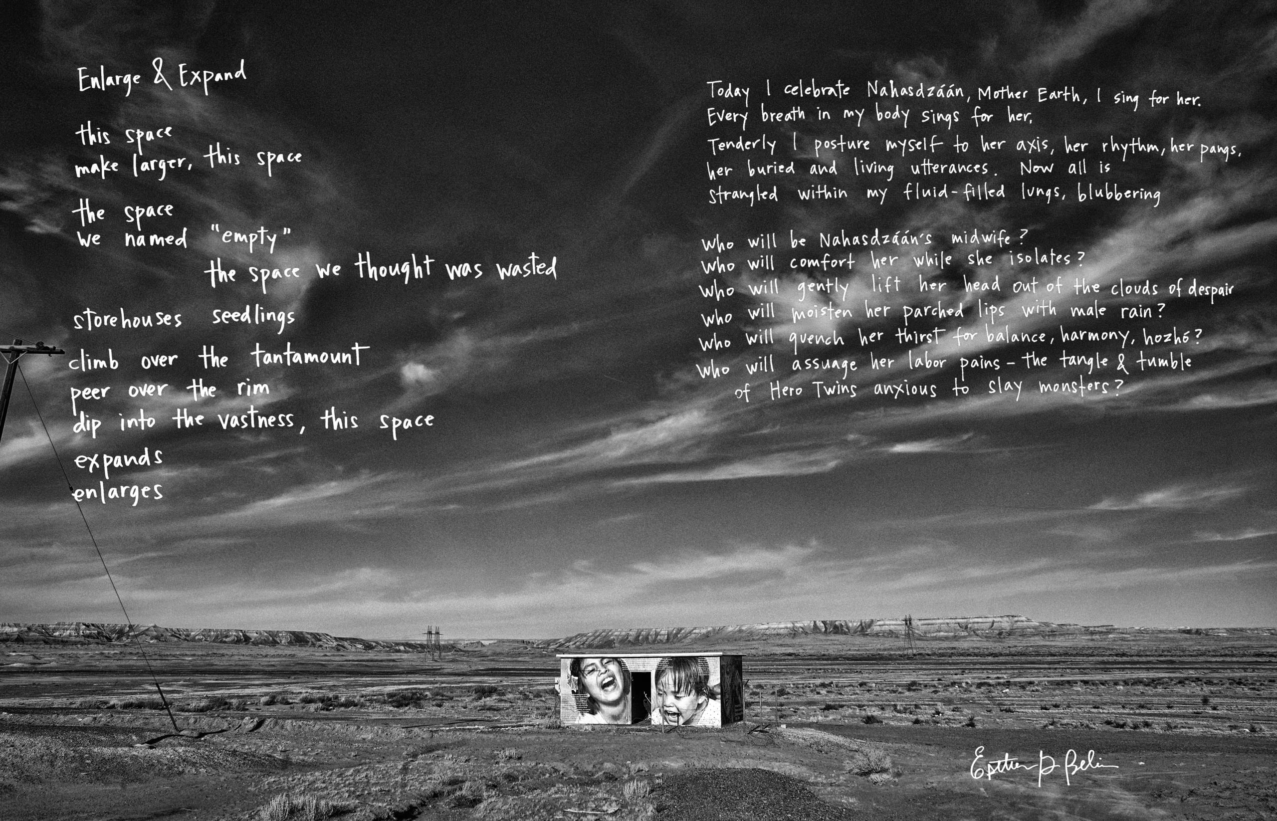 Black and white photo of sky occupying two-thirds of frame; a small, flat-roofed, rectangular building at center front is wrapped in an enlarged black and white photographic mural of two young children, laughing; a handwritten poem is printed in white text against the sky
