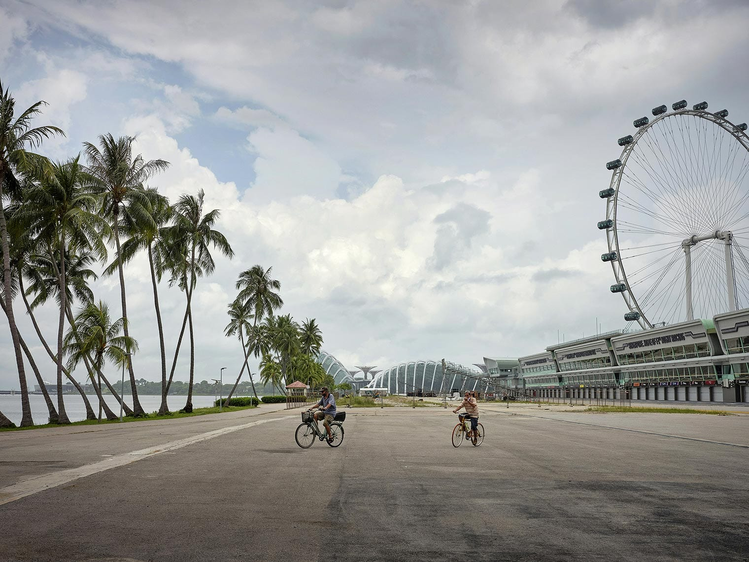 Two cyclists on an empty road surrounded by palm trees and a ferris wheel