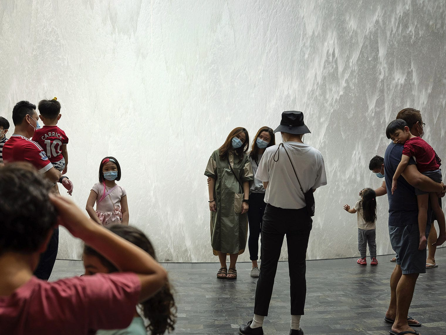 Several masked people stand, look, and take pictures in front of a wall of water