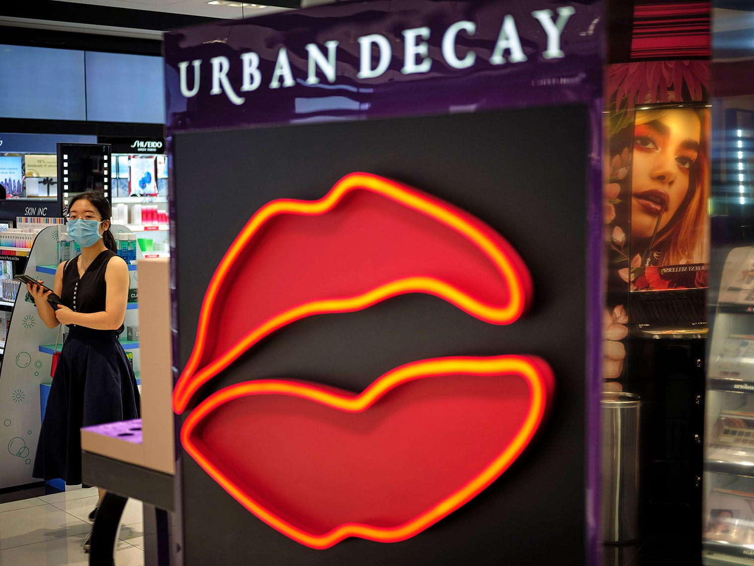 "Sign with neon-outlined parted lips that reads ""Urban Decay"" at entrance to Sephora store, with masked woman in background looking at the camera"