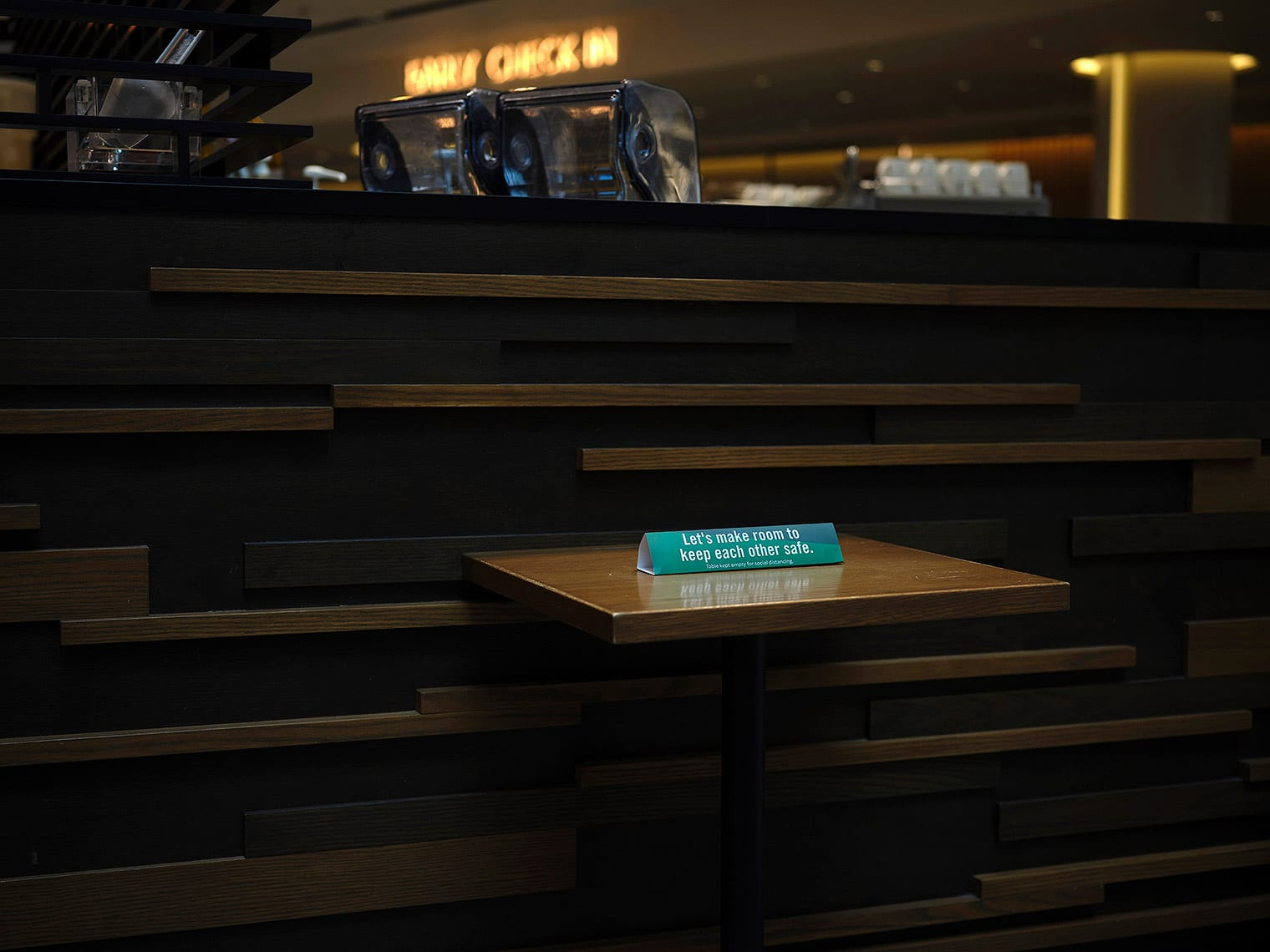 "Small green sign reading ""Let's make room to keep each other safe"" on a wooden restaurant table"