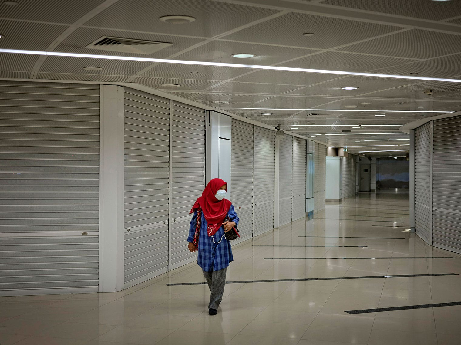 Woman wearing a face mask and red hijab walks down a hallway past several shuttered shopss