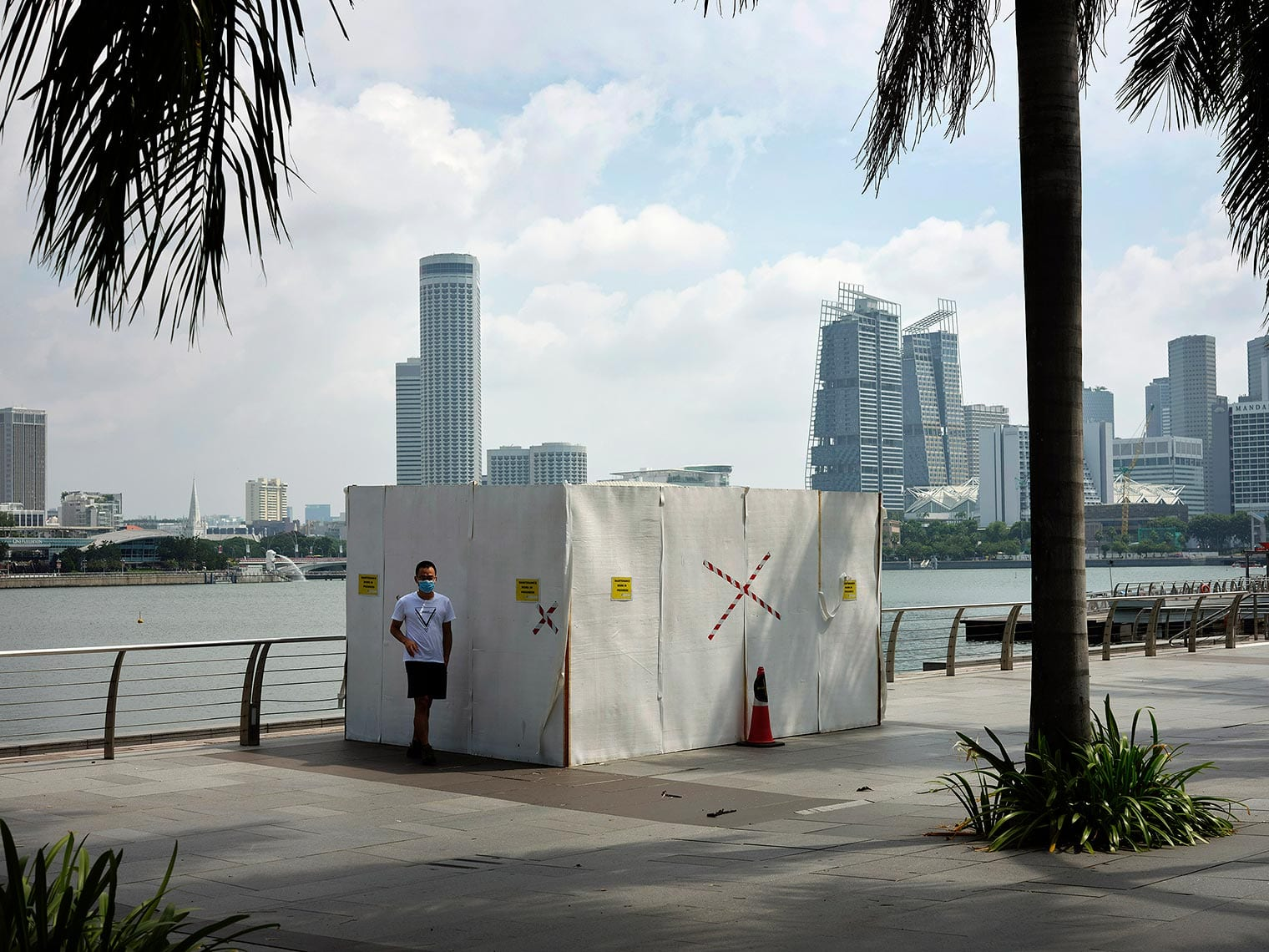 A lone masked person stands before a taped-off small building by the water in Singapore