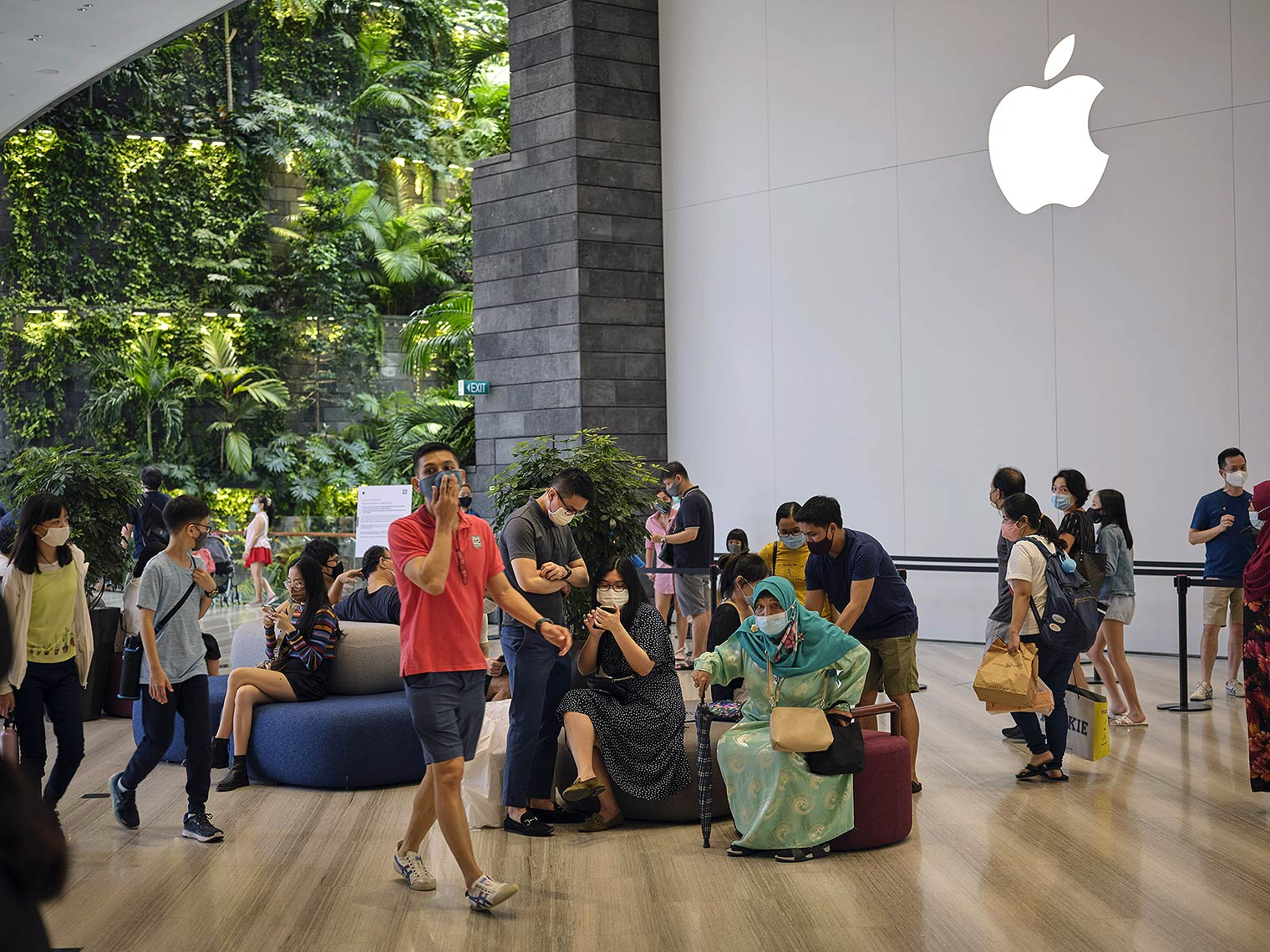 Masked shoppers sitting and standing in a mall, with a greenery-covered wall to the left and a large glowing Apple-brand logo on the wall to the right