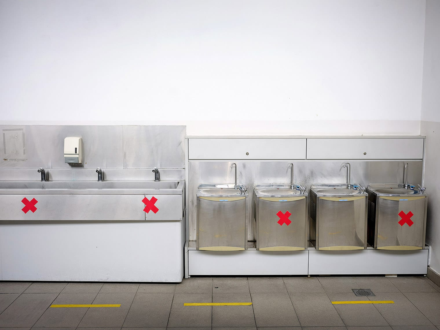 Seven water fountains lined up against the wall; every other foundatin is marked with a red X in tape