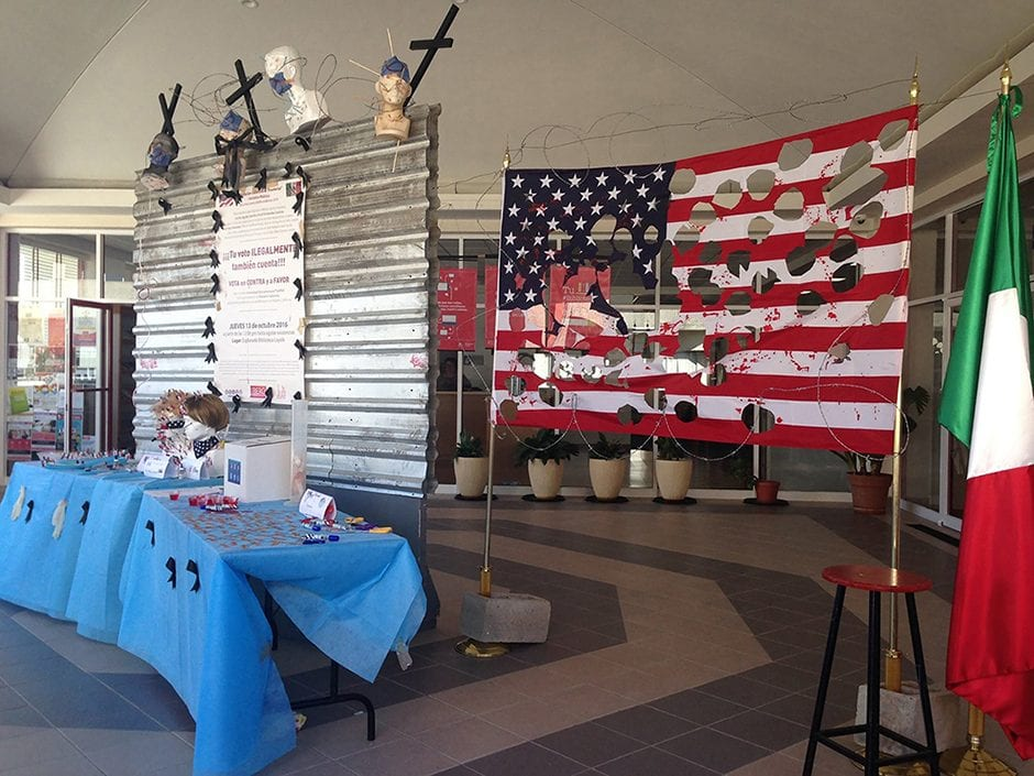 A table with ballots and a ballot box in front of a metal wall topped with crucifixes and barbed wire, next to an American flag with holes cut out of it