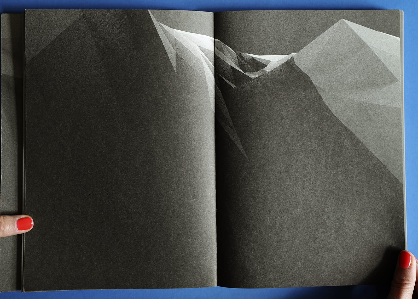 Open-book spread of Imaginary Explosions. Black-and-white graphic of mountain topography.