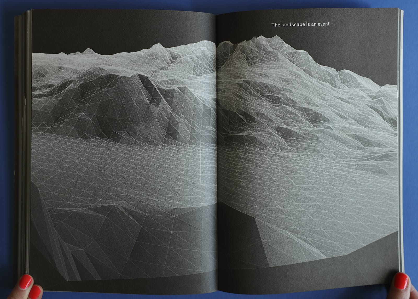 """Open-book spread of Imaginary Explosions, page 87. Above black-and-white graphic of mountain topography, text reads, """"The landscape is an event. (or is it)"""""""