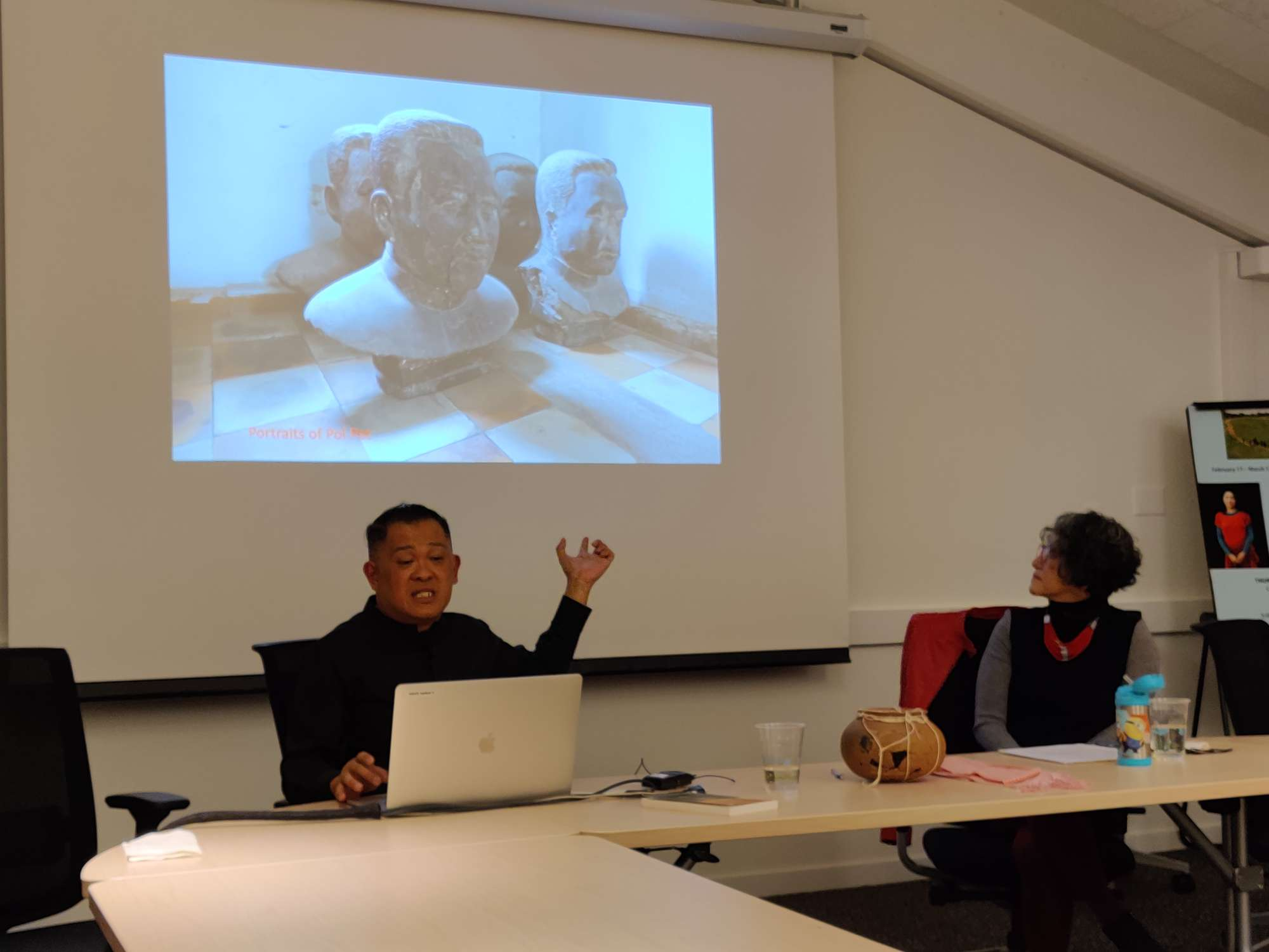 Color photograph of two people sitting in front of a white screen. An image of a sculpted portrait is projected on the screen.