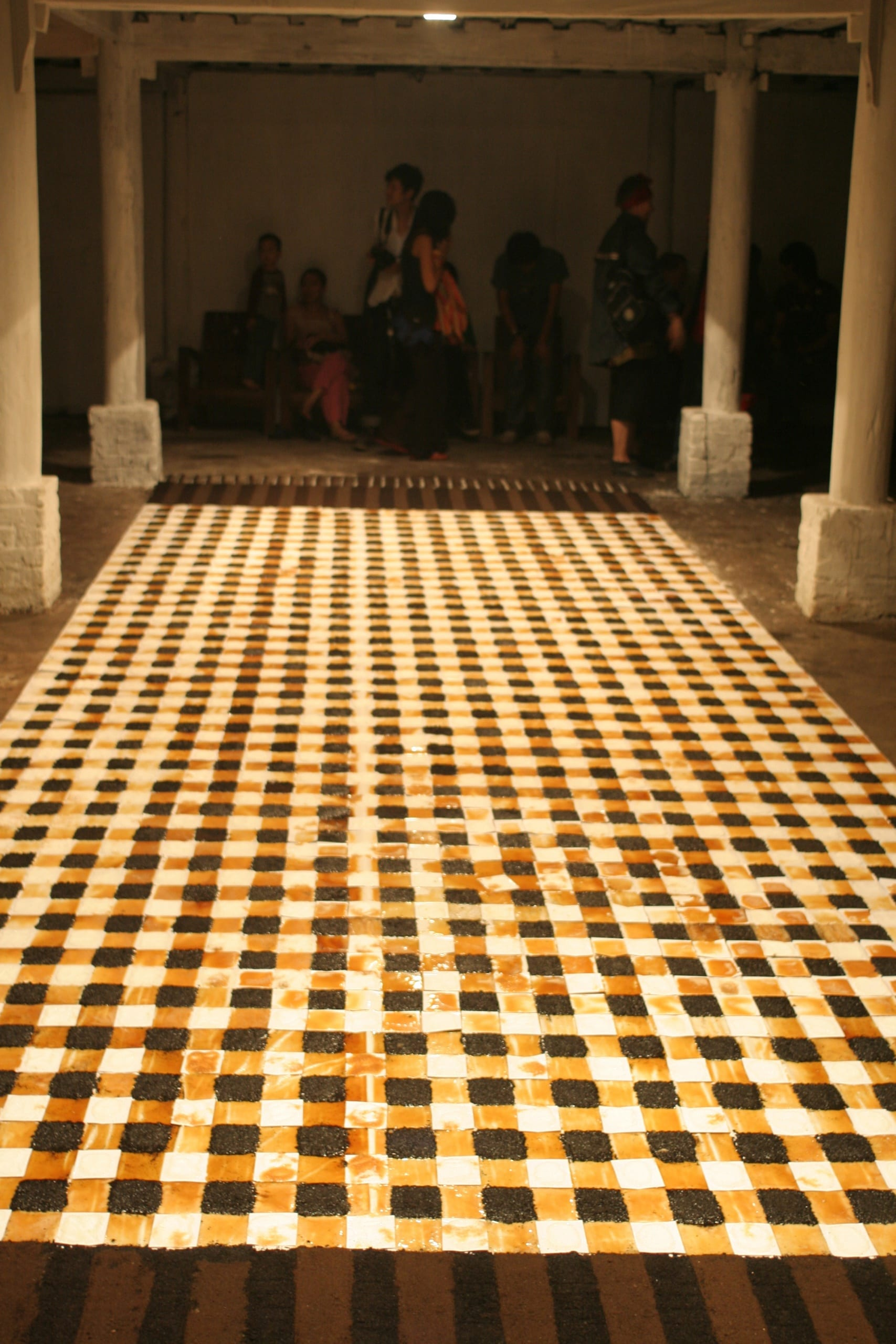 Color photograph of an artwork created on the floor that mimics a checkered scarf. The squares in the grid are painted using sugar and coffee grounds in alternating colors: dark brown, white, and light brown.
