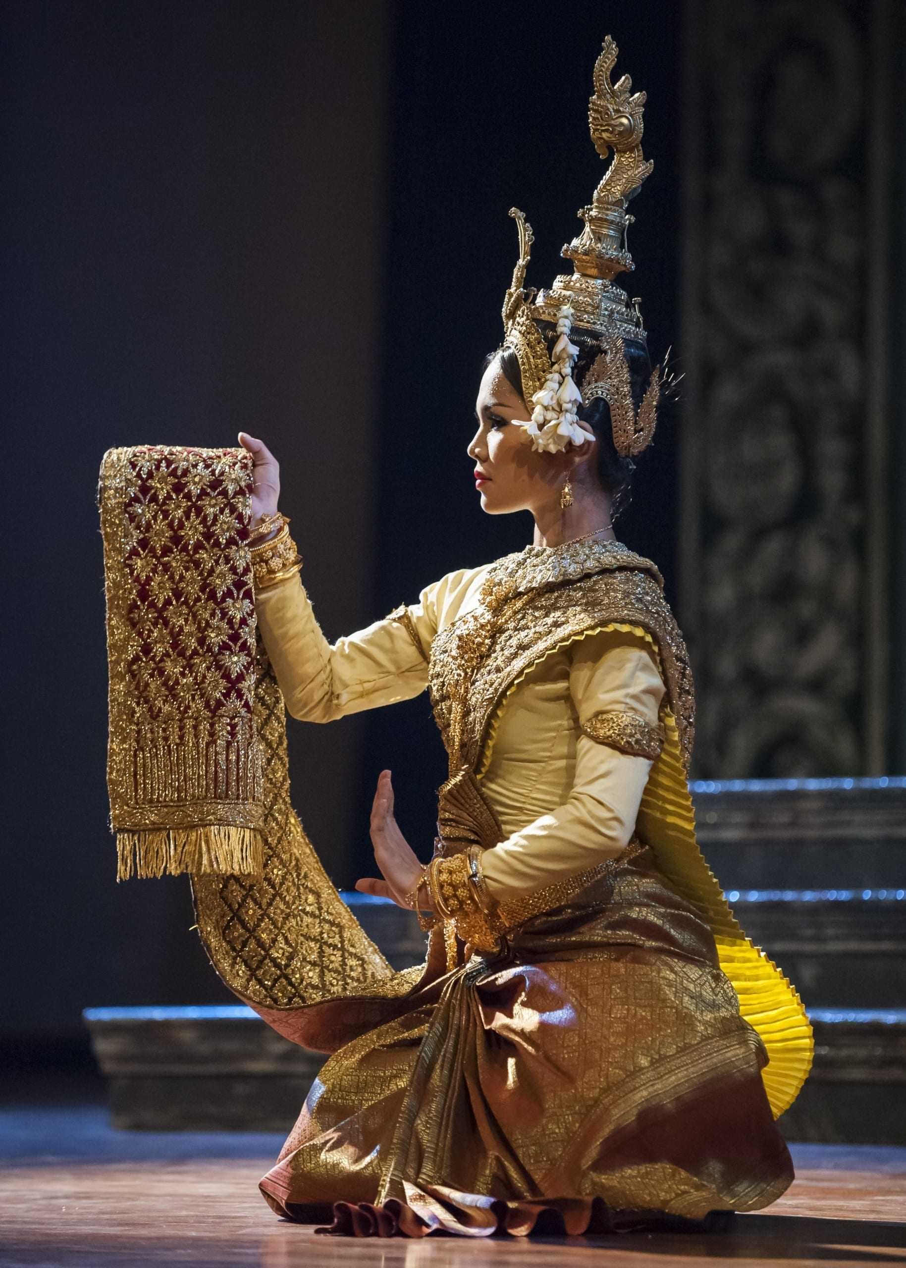 Color photograph of a dancer dressed in glittering gold-embroidered costume, crouching down and holding up a scarf. She wears a tall gold crown in the shape of an undulating serpent.
