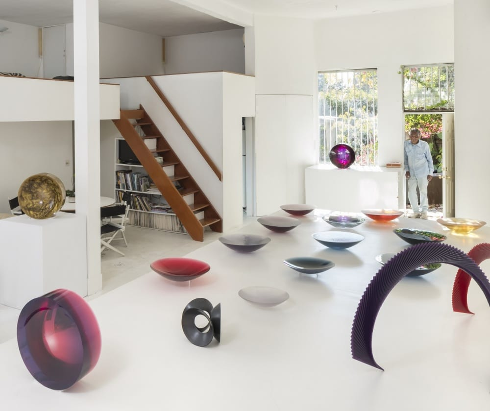 Fred Eversley stands in the doorway of his white, modern studio surrounded by examples of his colorful plastic sculptures sprawled across a table, on a pedestal, and in front of a window.