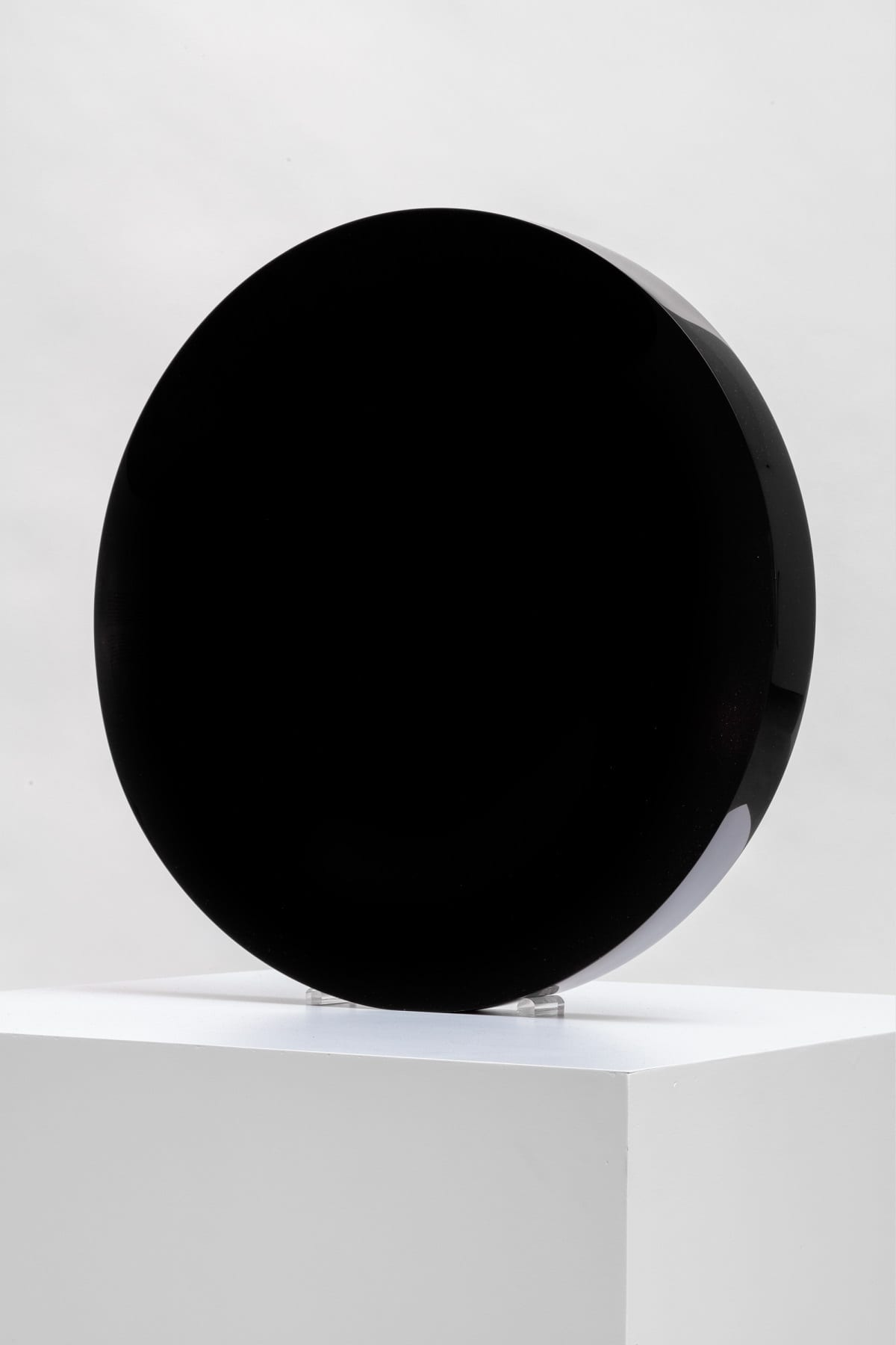 A round, cylindrical cast-polyester sculpture by Fred Eversley. It is dark black, with no details detectable through the rich color.