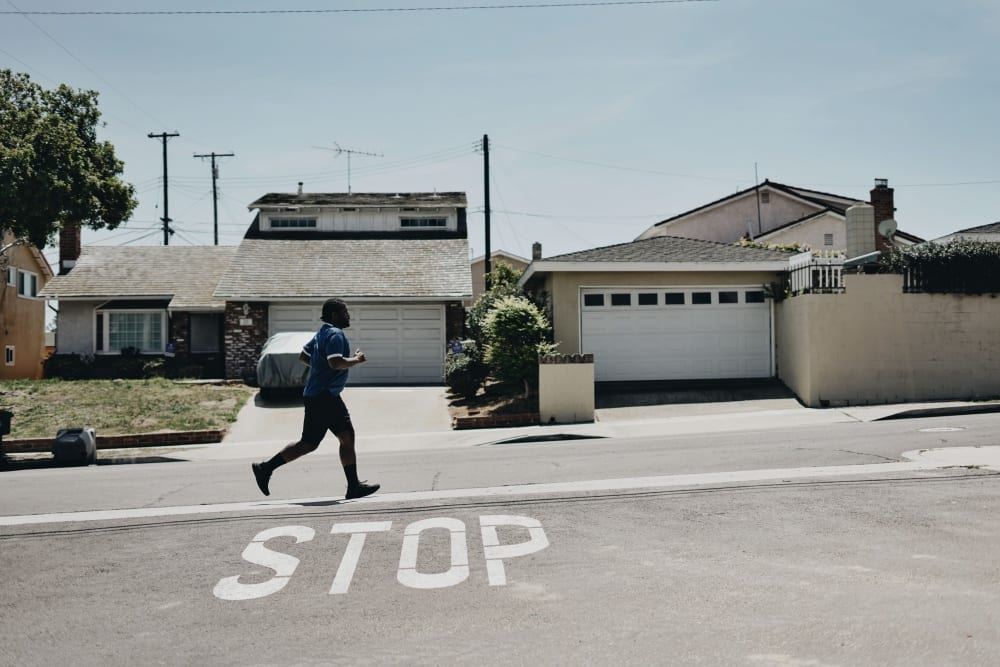 A man runs along a sidewalk in the bright sunlight with houses behind him and the word STOP painted on the ground