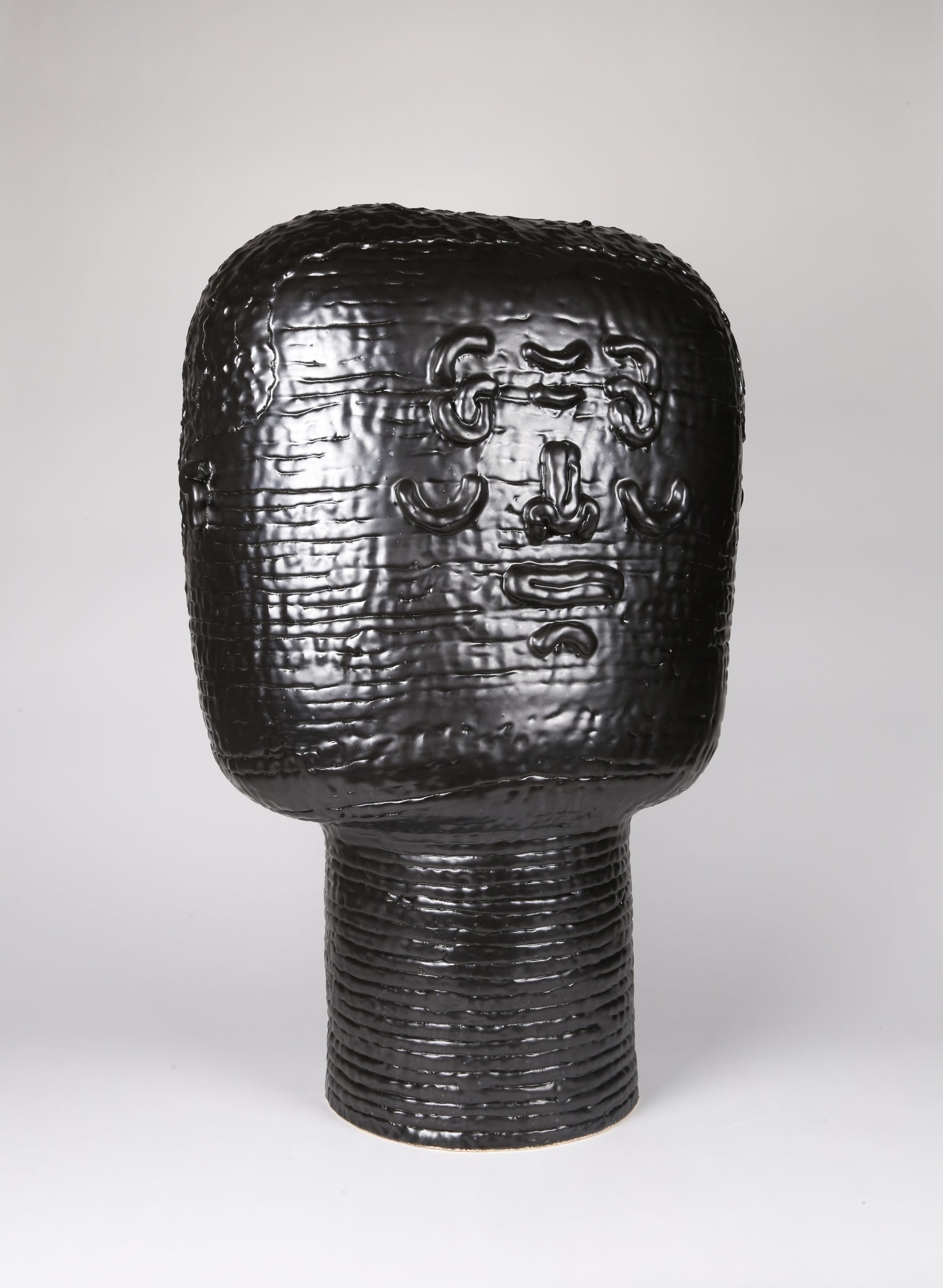 Color photograph with an oblique three-quarters view of an abstract ceramic portrait head that appears to be made from a long coil of clay. The head is sculpted to appear square or block-like. The outlines of two eyes, a nose, a mouth, and two ears are affixed to its surface, and the figure seems to be expressing a shy grin. The rear of the portrait details the texture of the figure's short cropped hair. The object is monochromatic (black), with a slight sheen to the glaze.