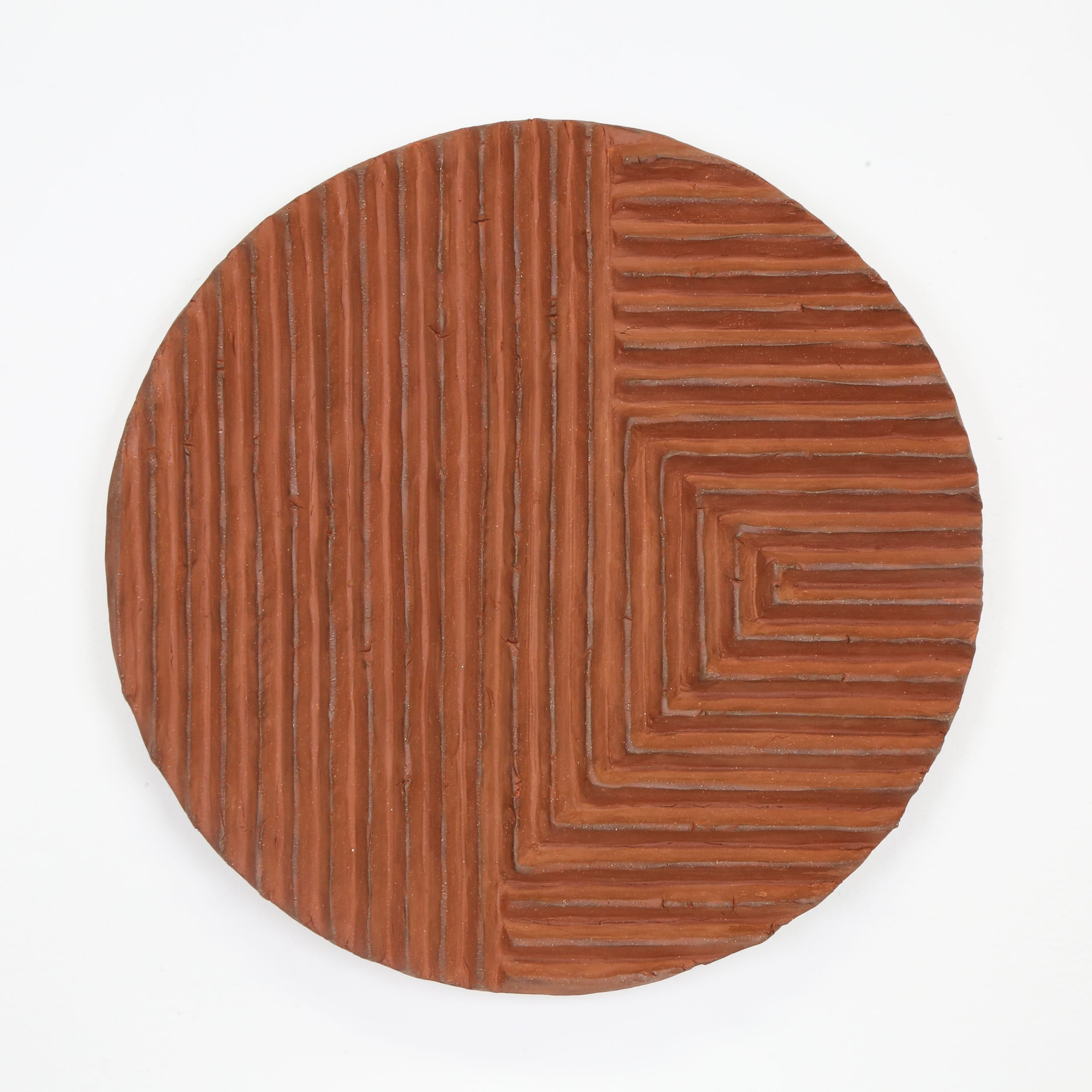 Color photograph of a terra-cotta disk with a series of raised, parallel lines sculpted onto its front. The lines run up and down vertically on the left, and toward the object's right the lines are horizontal. The object appears to be unglazed.