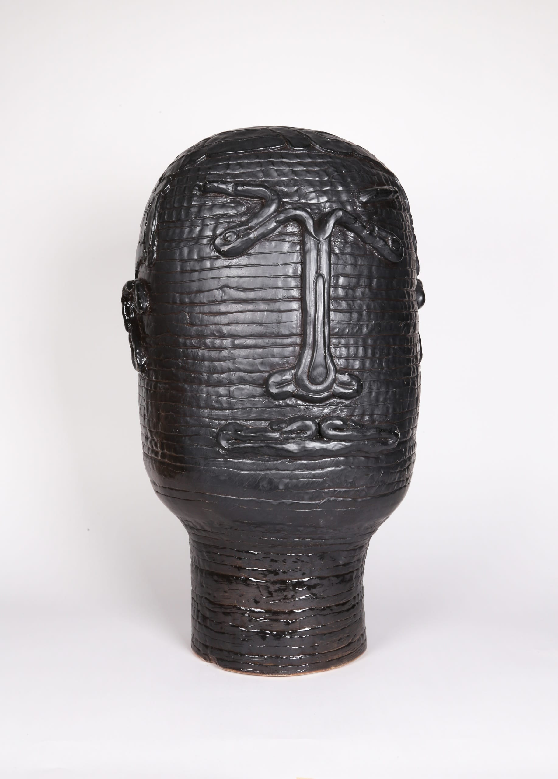 Color photograph with a frontal view of an abstract ceramic portrait head that appears to be made from a long coil of clay. The outline of two eyes, a nose, a mouth, and two ears are affixed to its surface. The object is a monochromatic black with a slight sheen to the glaze.