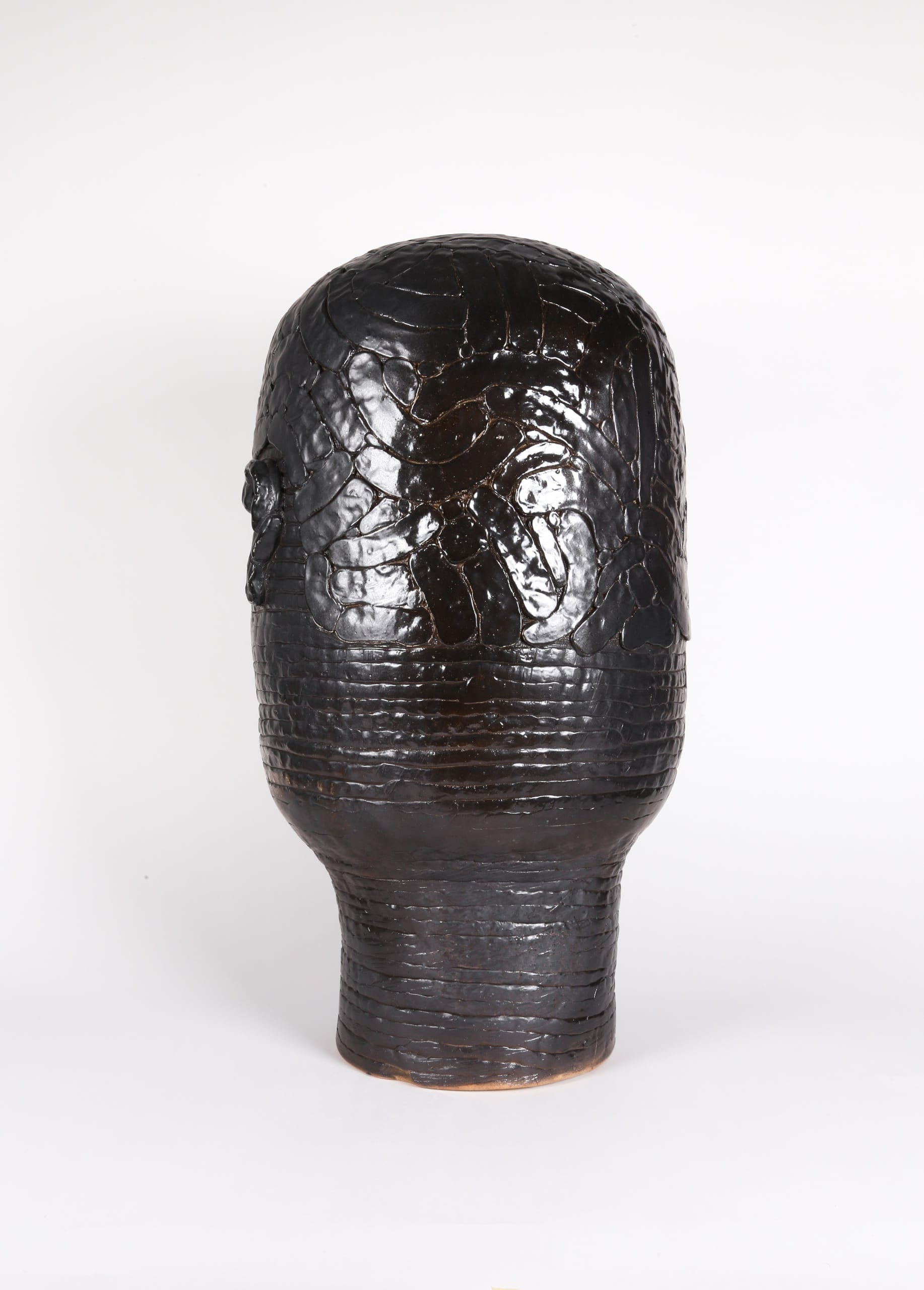 Color photograph with a back view of an abstract ceramic portrait head that appears to be made from a long coil of clay. The outline of hair is affixed to its surface. The object is a monochromatic black with a slight sheen to the glaze.