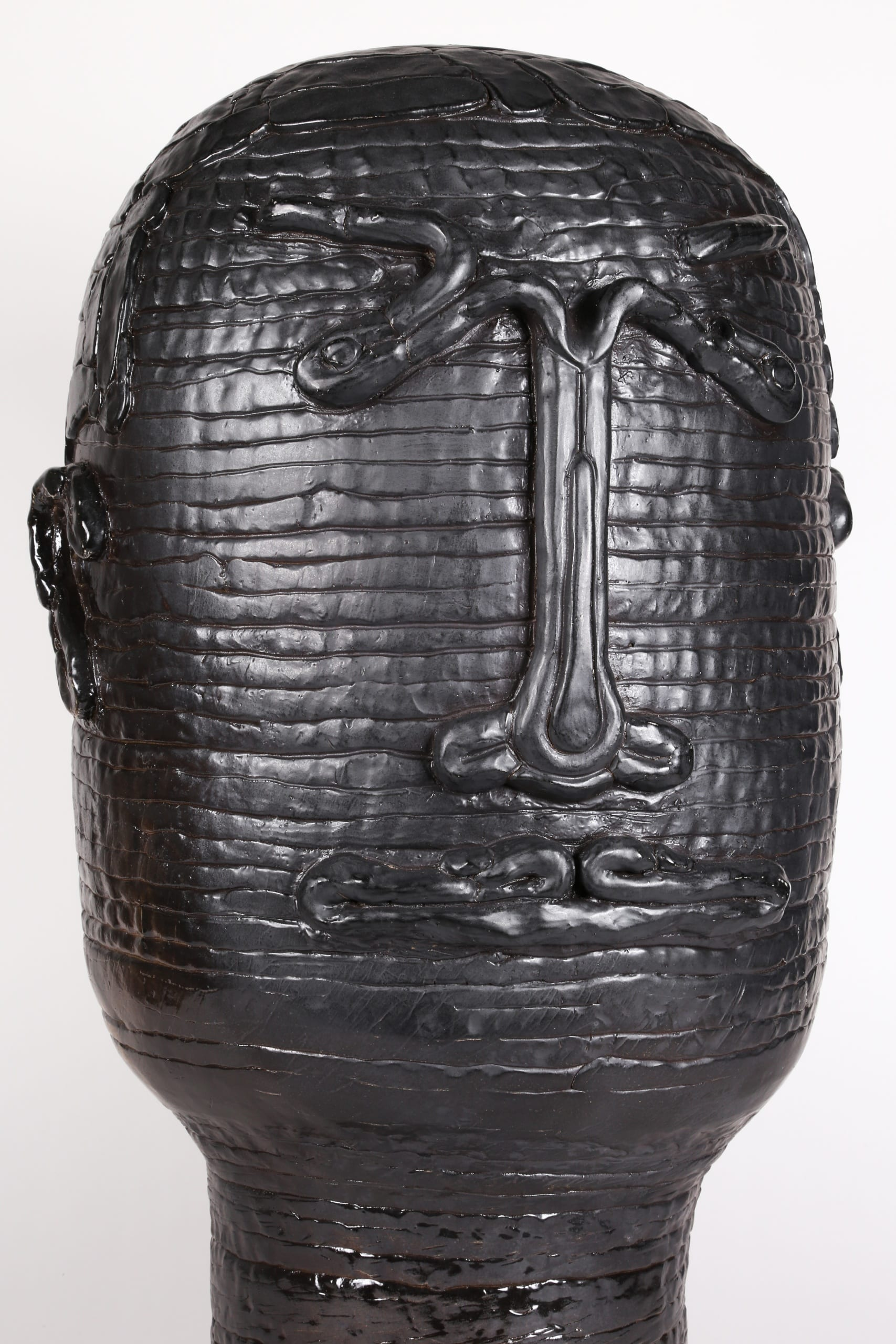 Color photograph of an abstract ceramic portrait head that appears to be made from a long coil of clay, showing an up-close view of the object's front so the clay's texture is more visible. The outline of two eyes, a nose, a mouth, and two ears are affixed to its surface. The object is a monochromatic black with a slight sheen to the glaze.