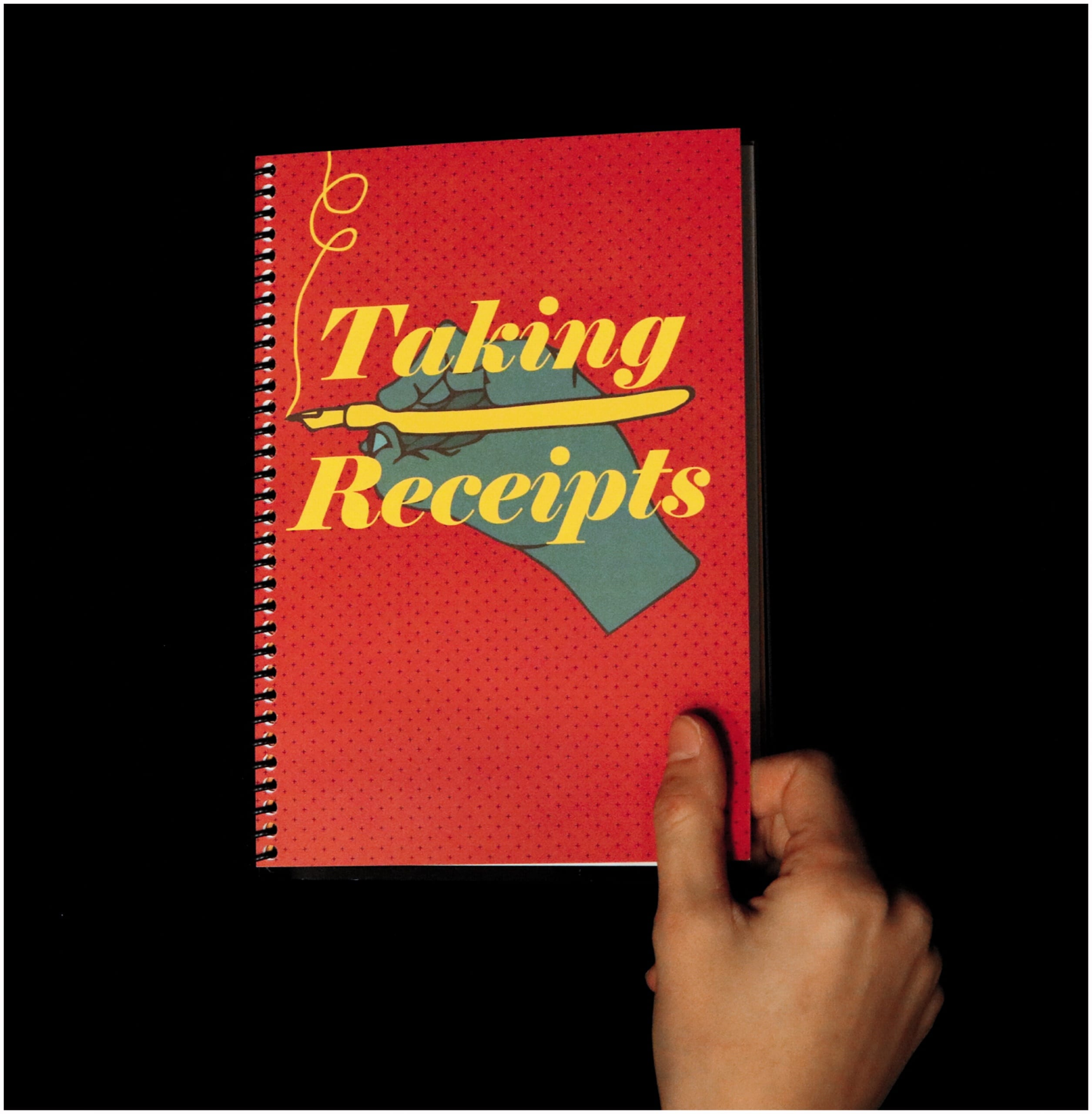 """Color photo of a hand opening a spiral-bound notebook. The cover of the notebook is red, and featuers an illustration of a hand drawing something with a yellow pen. The text on the front reads """"Taking Receipts."""""""