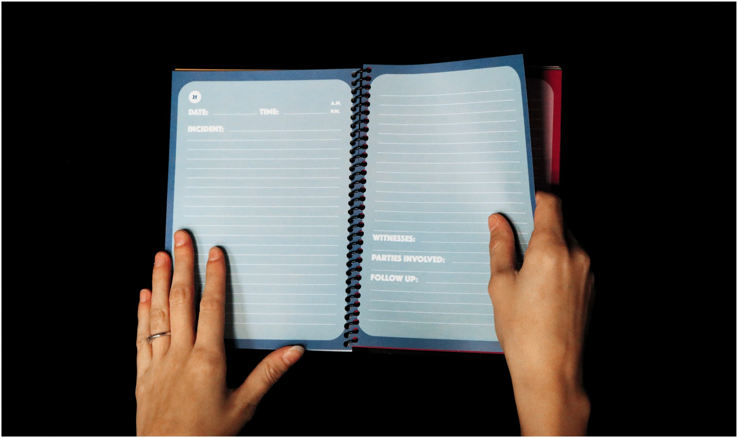 """Color photo of two hands grasping an open spiral-bound notebook. The light-blue pages are ruled and feature a template, with slots for the following information: """"Date,"""" """"Time,"""" """"A.M./P.M.,"""" """"Incidents,"""" """"Witnesses,"""" """"Parties Involved,"""" and """"Follow Up."""""""