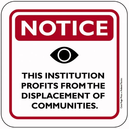 """A bold, red-and-white sign in the style of a """"Neighborhood Watch"""" sign. At the top reads """"NOTICE"""" in bold letters; in the middle is the black-and-white icon of an open eye. Under that reads, """"THIS INSTITUTION PROFITS FROM THE DISPLACEMENT OF COMMUNITIES."""""""