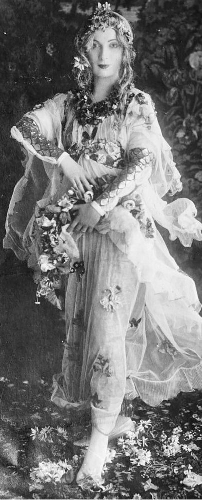 In this photograph, Hazel Lavery is dressed up as Flora from Botticelli's painting Primavera. She wears a dress and head covering with flowers sewn onto them.