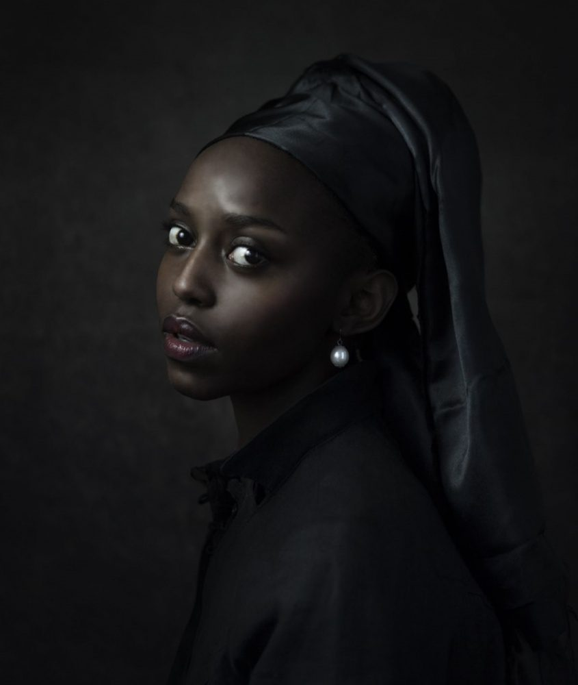 A woman in three-quarters view, dressed in a black headdress and tunic, looks over her left shoulder to exchange gazes with the viewer. Her black skin is luminous. She is a re-creation of Vermeer's Girl with a Pearl Earring and a celebration of Blackness.