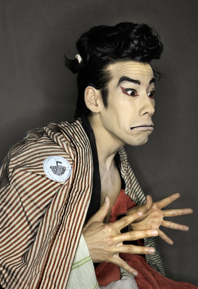 Kento Mizuno, in collaboration with Katie Mizuno, re-created Sharaku's woodblock print of a kabuki actor. Kento Mizuno, adorned with dramatic make-up, appears in three-quarters view with his hands extended before him.